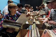 People browse through boxes of records in the New York City Public Library for the Performing Arts at Lincoln Center, Friday, Aug. 9, 2013. The library is selling 22,000 duplicate vinyl records that were preserved in mint condition to raise money for the expansion of the library. (AP Photo/Richard Drew)