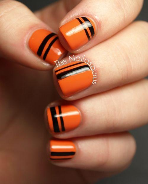 "<p>If you prefer <a href=""https://www.goodhousekeeping.com/beauty/nails/g3546/what-your-nail-art-says-about-you/"" rel=""nofollow noopener"" target=""_blank"" data-ylk=""slk:simplicity to complex designs"" class=""link rapid-noclick-resp"">simplicity to complex designs</a>, try a modern look that features classic orange and black. </p><p><a class=""link rapid-noclick-resp"" href=""https://www.amazon.com/HuntGold-Strip-Sticker-Decoration-Manicure/dp/B00IUAD1E4/ref=sr_1_5?tag=syn-yahoo-20&ascsubtag=%5Bartid%7C10055.g.1421%5Bsrc%7Cyahoo-us"" rel=""nofollow noopener"" target=""_blank"" data-ylk=""slk:SHOP BLACK NAIL TAPE"">SHOP BLACK NAIL TAPE</a></p><p><em><a href=""http://www.thenailasaurus.com/2012/10/31dc2012-day-12-stripes.html"" rel=""nofollow noopener"" target=""_blank"" data-ylk=""slk:Get the tutorial at The Nailasaurus »"" class=""link rapid-noclick-resp"">Get the tutorial at The Nailasaurus »</a></em><br> </p>"