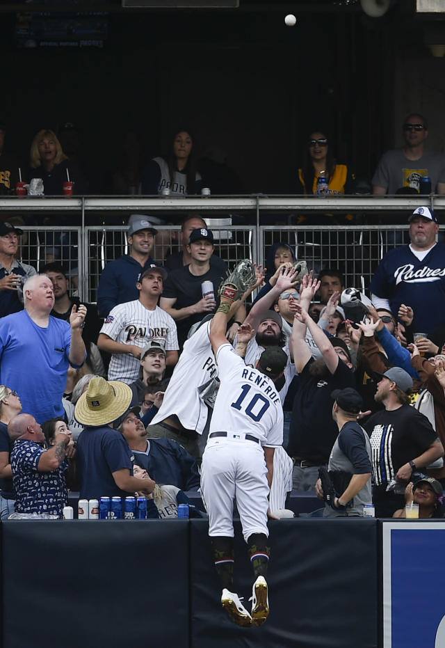 San Diego Padres left fielder Hunter Renfroe jumps onto the outfield padding to try and catch a three-run home run by Pittsburgh Pirates' Josh Bell during the third inning of a baseball game in San Diego, Saturday, May 18, 2019. (AP Photo/Kelvin Kuo)