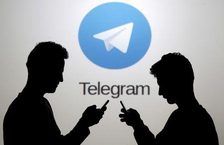 FILE PHOTO: Men pose with smartphones in front of a screen showing the Telegram logo in this picture illustration November 18, 2015. REUTERS/Dado Ruvic/File Photo - RTS18EPF