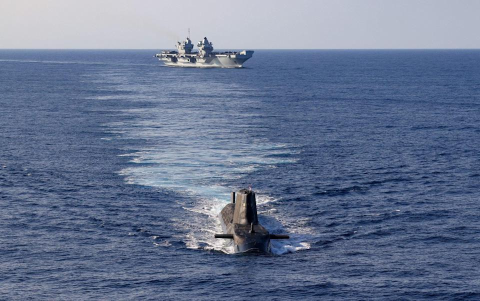 An Astute Class Submarine on the surface with HMS Queen Elizabeth in the background - Royal Navy