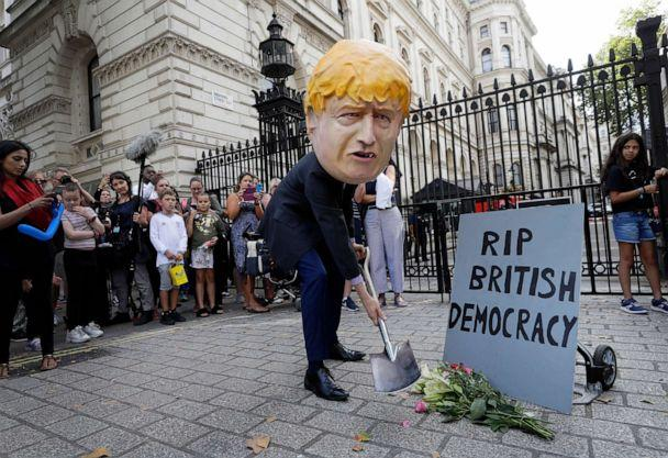 PHOTO: A man in a giant Boris Johnson head digs a grave at the foot of a pretend tombstone outside Downing Street in London, Aug. 28, 2019. (Kirsty Wigglesworth/AP)