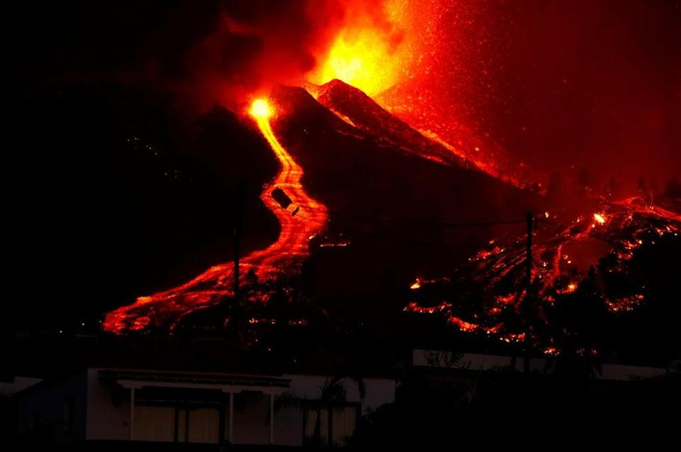 Lava flows next to a house on Sunday night (REUTERS)