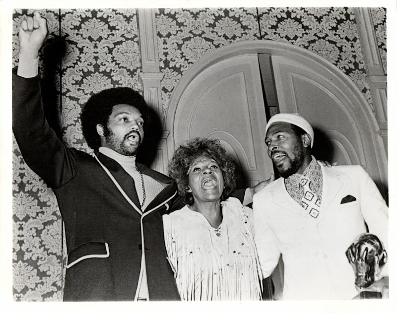 "Marvin Gaye, clutching one of three Image Awards received at the NAACP's 5th Annual Image Awards Show in Hollywood, sings ""Lift Every Voice and Sing"" with awards chairman Maggie Hathaway and the Rev. Jesse L. Jackson on Nov. 21, 1971"
