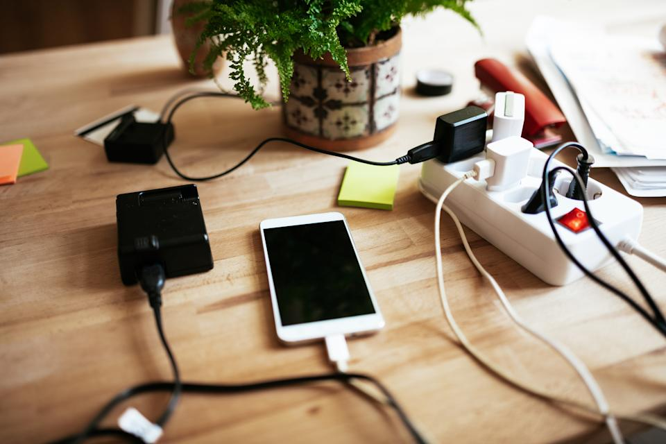 Mobile phone and batteries on charger, on high resolution 45 Mpx photo, carefully processed and left space for copy.