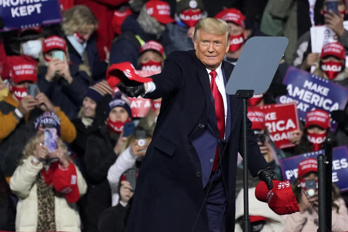 President Donald Trump tosses ball caps to supporters as he arrives for a campaign rally at the Williamsport Regional Airport in Montoursville, Pa, Saturday, Oct. 31, 2020. (AP Photo/Gene J. Puskar)