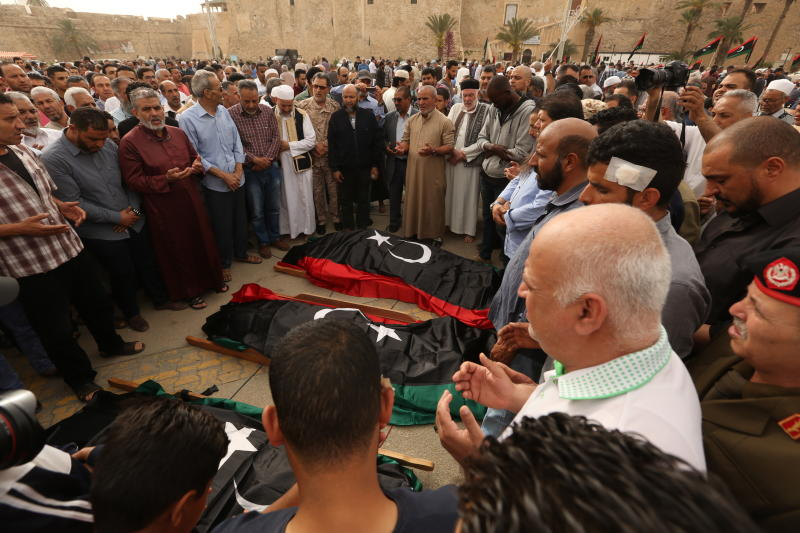 FILE - In this April 24, 2019 file photo, mourners pray for fighters killed in airstrikes by warplanes of Field Marshal Khalifa Hifter's forces, in Tripoli, Libya. Officials in Libya's U.N.-backed administration say they plan to present evidence to Moscow of Russian mercenaries fighting alongside their adversary in their country's war. Libyan officials say up to 800 fighters from the Russian private security contractor Wagner Group have joined the forces of Hifter, the commander of forces battling for months trying to capture Libya's capital, Tripoli. (AP Photo/Hazem Ahmed, File)