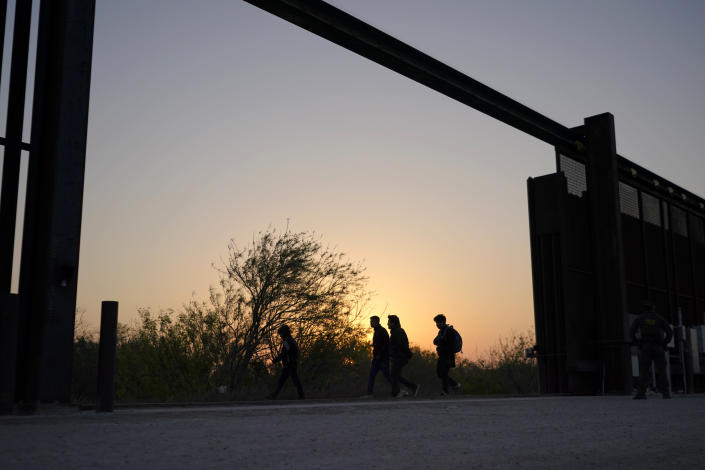 """Migrants walk near a gate on the U.S.-Mexico border wall after they were spotted by a U.S. Customs and Border Protection agent and taken into custody while trying to cross, Sunday, March 21, 2021, in Abram-Perezville, Texas. The fate of thousands of migrant families who have recently arrived at the Mexico border is being decided by a mysterious new system under President Joe Biden. U.S. authorities are releasing migrants with """"acute vulnerabilities"""" and allowing them to pursue asylum. But it's not clear why some are considered vulnerable and not others. (AP Photo/Julio Cortez)"""