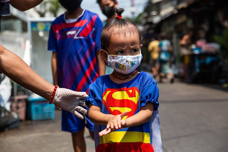 BANGKOK, THAILAND - APRIL 22:  A little Thai girl in the Bonkai community in Bangkok's Pathumwan district uses hand sanitizer as she stands in a social distancing queue to recieve food, water and face mask from the Poh Tek Tung Foundation on April 22, 2020 in Bangkok, Thailand.  The Poh Tek Tung Foundation, which primarily serves as a rescue organization is doing daily donations to poorer communities throughout Bangkok during the lockdown imposed by the Thai government as an effort to stop the spread of Covid-19. Due to the economic impact of the coronavirus pandemic, many community members have lost work and jobs due to the shutdown of businesses throughout the city and rely on donations for daily food. Thailand currently has 2,826 confirmed cases of Covid-19. (Photo by Lauren DeCicca/Getty Images)