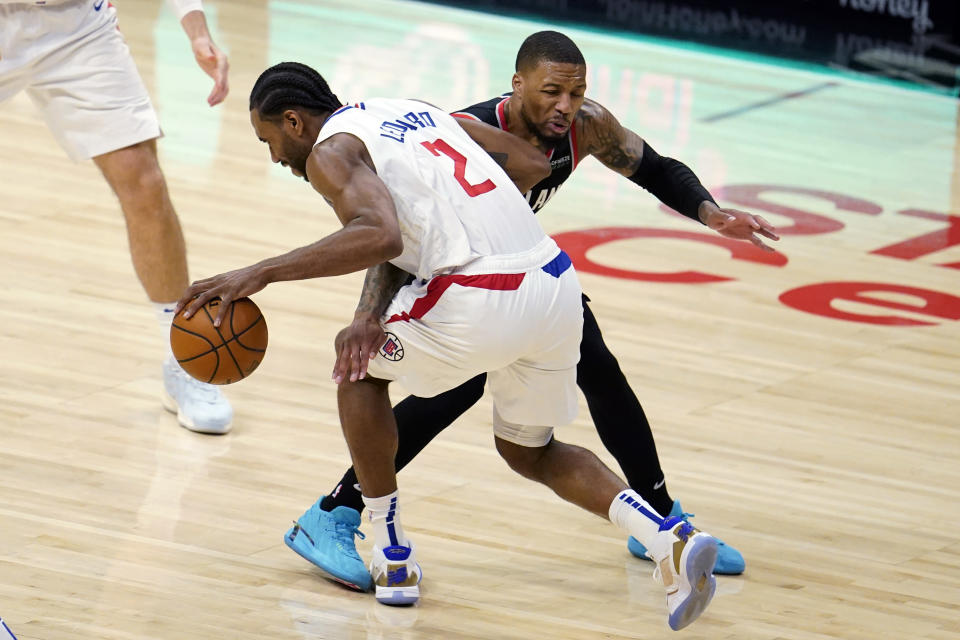 Los Angeles Clippers forward Kawhi Leonard (2) is defended by Portland Trail Blazers guard Damian Lillard during the first half of an NBA basketball game Tuesday, April 6, 2021, in Los Angeles. (AP Photo/Marcio Jose Sanchez)