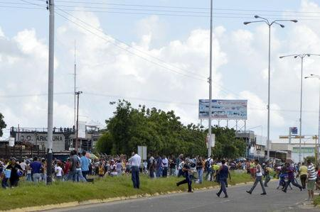 People carry goods looted from a supermarket in San Felix in the state of Bolivar