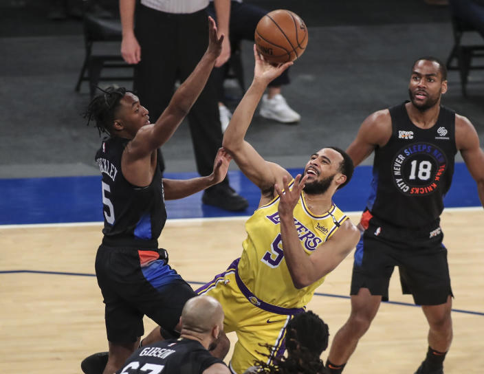 Los Angeles Lakers guard Talen Horton-Tucker, center, shoots over New York Knicks guard Immanuel Quickley, left, in the first quarter of an NBA basketball game at Madison Square Garden in New York, Monday, April 12, 2021. (Wendell Cruz/Pool Photo via AP)