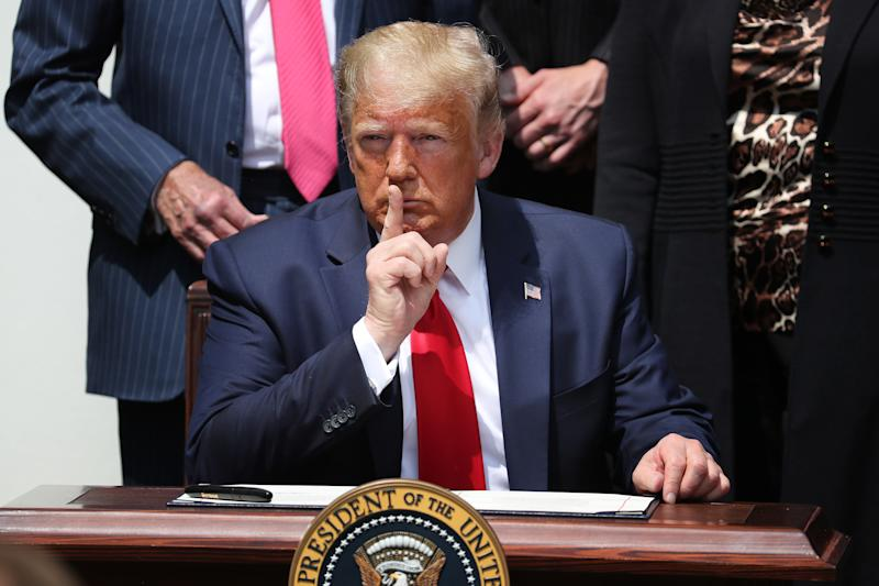 President Trump shushes journalists before signing the Paycheck Protection Program Flexibility Act in June 2020. (Chip Somodevilla/Getty Images)