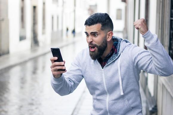 Bearded man yelling at cellphone