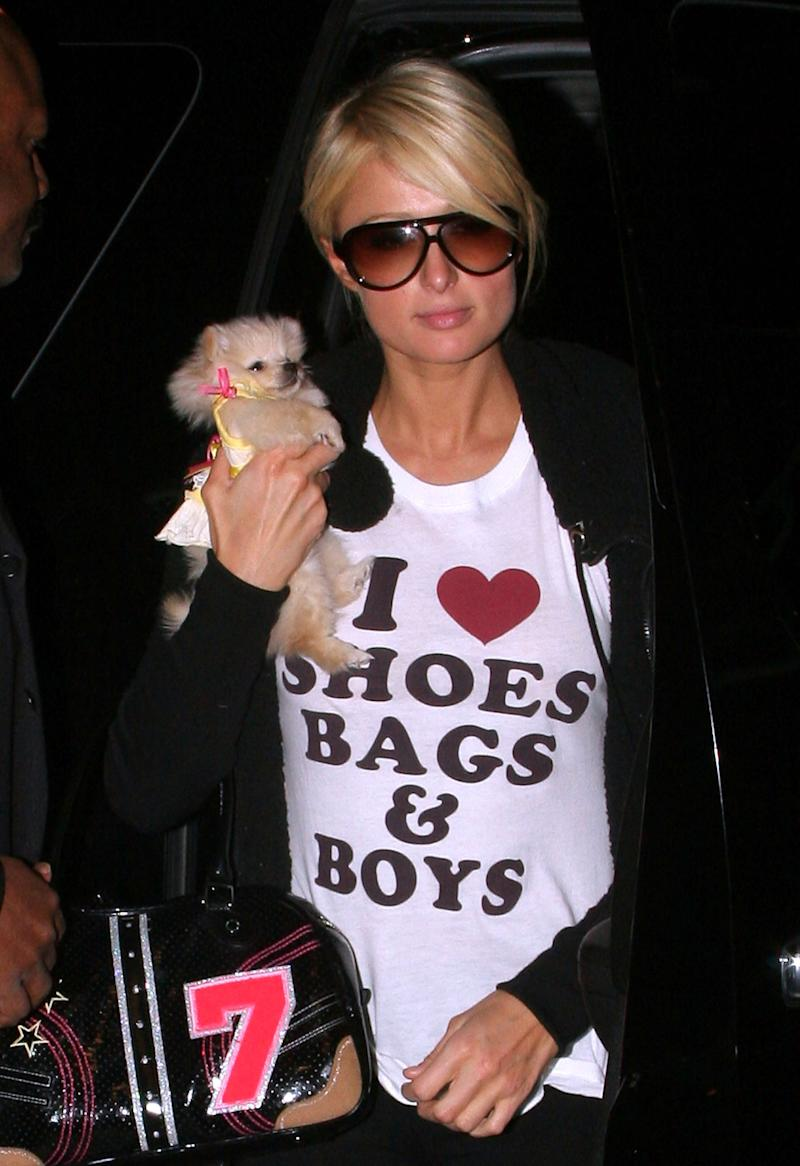 """Paris Hilton wears a shirt that says, """"I love shoes, bags, and boys,"""" while out in New York City with her dog."""
