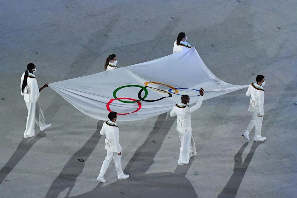 <p>An overview shows the Olympic flag being carried during the opening ceremony of the Tokyo 2020 Olympic Games, at the Olympic Stadium, in Tokyo, on July 23, 2021. (Photo by Antonin THUILLIER / AFP) (Photo by ANTONIN THUILLIER/AFP via Getty Images)</p>