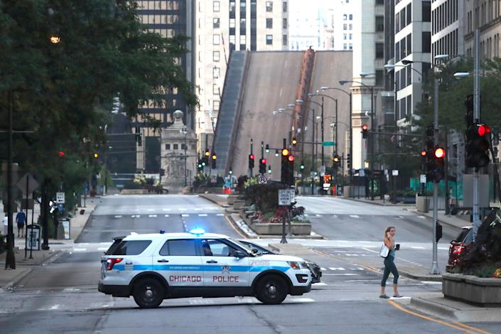 A pedestrian walks across Michigan Ave., Monday, Aug. 10, 2020, past a Chicago police department vehicle, a few blocks north of the raised Michigan Ave. bridge over the Chicago river after overnight vandalism in Chicago.