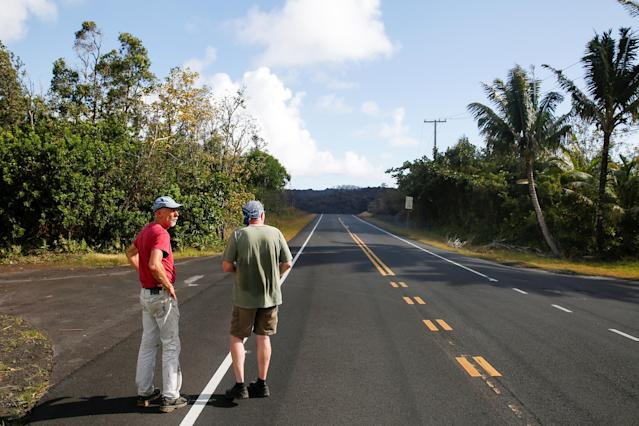 <p>Mark Clawson, 64, (L), and Tom McCarroll, 68, look at a lava flow near their homes outskirts of Pahoa during ongoing eruptions of the Kilauea Volcano in Hawaii, June 6, 2018. (Photo: Terray Sylvester/Reuters) </p>