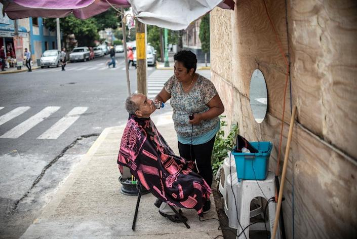 Stylist Xochilt de la Paz, who lost her mother and her business in the September 19, 2017 earthquake in Mexico City, works on a customers' stubble on the sidewalk in the city's Ninos Heroes neigborhood (AFP Photo/Pedro PARDO)