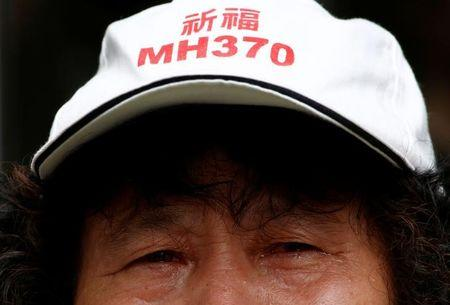 A family member of a passenger aboard Malaysia Airlines flight MH370 which went missing in 2014 reacts during a protest outside the Chinese foreign ministry in Beijing
