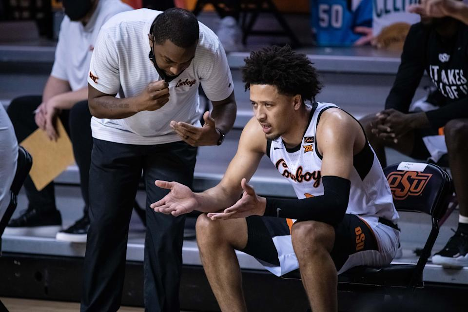 Oklahoma State coach Mike Boynton talks with guard Cade Cunningham during the game against the Texas on Feb. 6, 2021 in Stillwater, Okla.