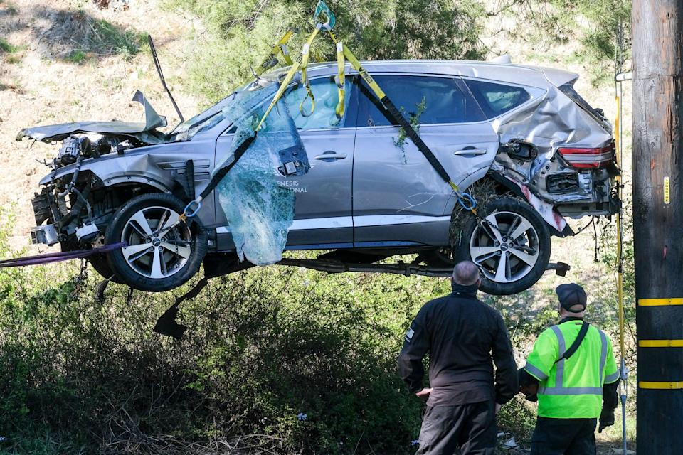 A crane is used to lift a vehicle following a rollover accident involving golfer Tiger Woods.