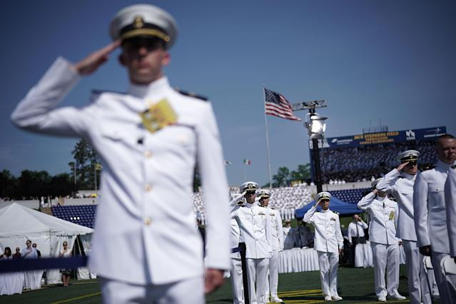 <p>Members of the U.S. Navy salute as they listen to the national anthem during a graduation ceremony at the Navy-Marine Corps Memorial Stadium of the U.S. Naval Academy May 25, 2018 in Annapolis, Md. (Photo: Alex Wong/Getty Images) </p>