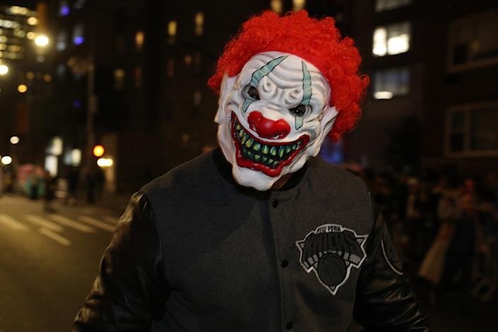 A reveler in a creepy clown mask marches in the the Village Halloween Parade in New York City. (Photo: Gordon Donovan/Yahoo News)