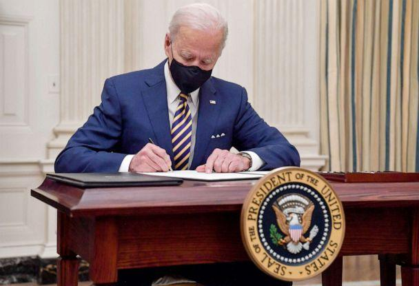 PHOTO: President Joe Biden signs executive orders for economic relief to Covid-hit families and businesses in the State Dining Room of the White House in Washington, on Jan. 22, 2021. (Nicholas Kamm/AFP via Getty Images)