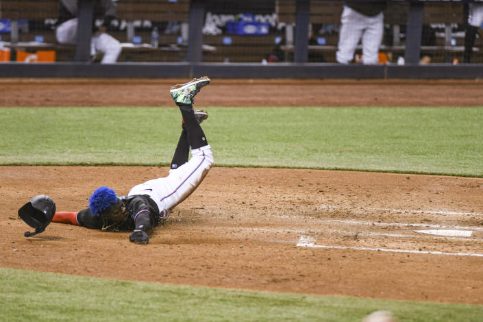 Miami Marlins' Jazz Chisholm Jr. scores on a sacrifice fly by Chad Wallach during the fourth inning of the team's baseball game against the Tampa Bay Rays, Saturday, April 3, 2021, in Miami. (AP Photo/Gaston De Cardenas)