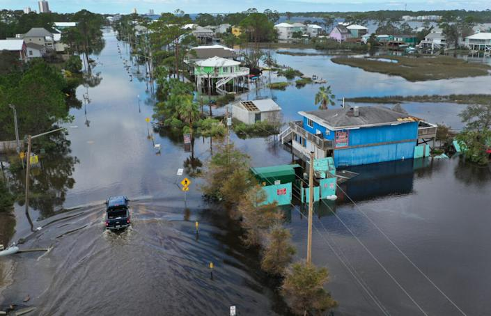 An aerial view from a drone shows a vehicle driving through a flooded street after Hurricane Sally passed through the area on September 17, 2020 in Gulf Shores, Alabama. The storm came ashore with heavy rain and high winds. (Photo by Joe Raedle/Getty Images)