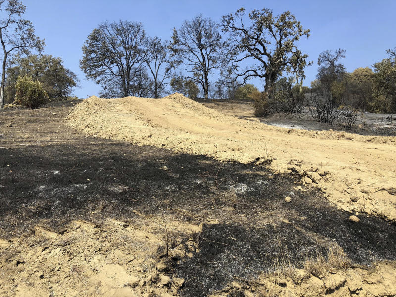 This photo taken Friday, Aug. 10, 2018 near Lakeport, Calif. shows a dirt path and dusty berms left behind when a bulldozer passed through private land in an effort to contain part of the largest wildfire on record in California. Even as flames continue chewing through forestland nearby, crews are working to repair the damage wrought not by flames but by firefighters trying to stop them. (AP Photo/Jonathan J. Cooper)