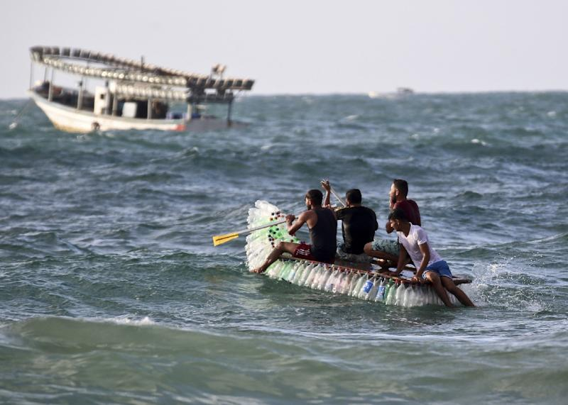 Palestinian fishermen on a boat made of 700 empty plastic bottles in waters off the southern Gaza Strip on August 14, 2018 (AFP Photo/SAID KHATIB)