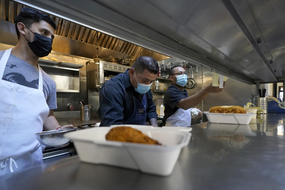 Teo Perez, from left, works in the kitchen with Jorge Morales and Jaime Hernandez at Brenda's French Soul Food in San Francisco, Wednesday, Dec. 9, 2020. In pre-pandemic days, Brenda's French Soul Food was always hopping, but everything came to a screeching halt on March 16, when San Francisco halted indoor dining to stop the spread of the coronavirus. It reopened for takeout and delivery, and Chef Proprieter Brenda Buenviaje is now shipping meals nationwide through a service called Goldbelly. (AP Photo/Jeff Chiu)