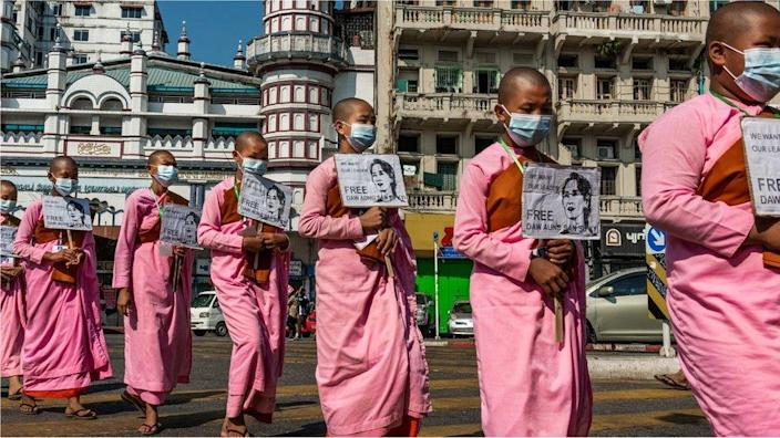 Buddhist monks hold placards featuring images of Aung San Suu Kyi during a protest on February 13, 2021 in Yangon, Myanmar.