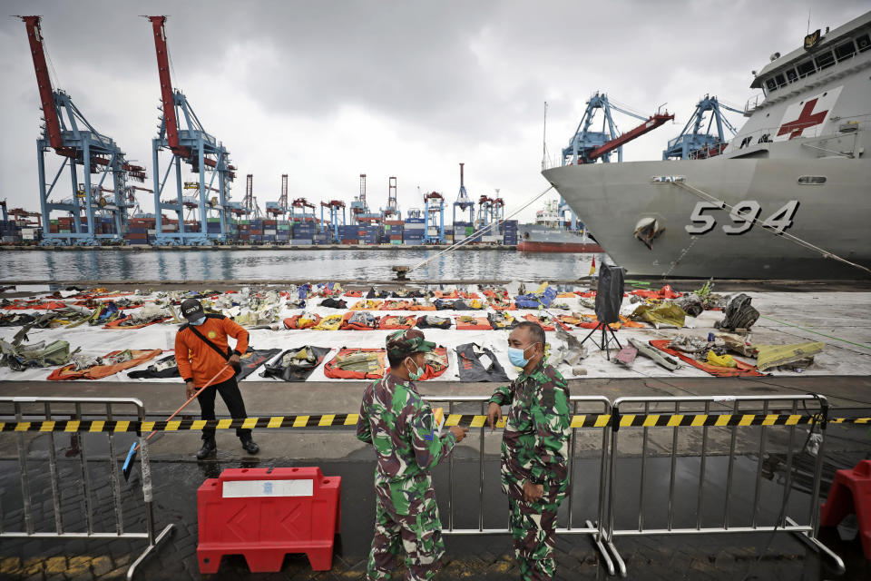 Navy personnel chat as a pieces of the Sriwijaya Air flight SJ-182 retrieved from the Java Sea where the passenger jet crashed on Jan. 9 are laid out for inspection by investigators, at the Tanjung Priok Port in Jakarta, Indonesia, Thursday, Jan. 21, 2021. Indonesian authorities on Thursday ended the search for the wreckage of the plane that nose-dived into the sea, killing all of its passengers on board. (AP Photo/Dita Alangkara)