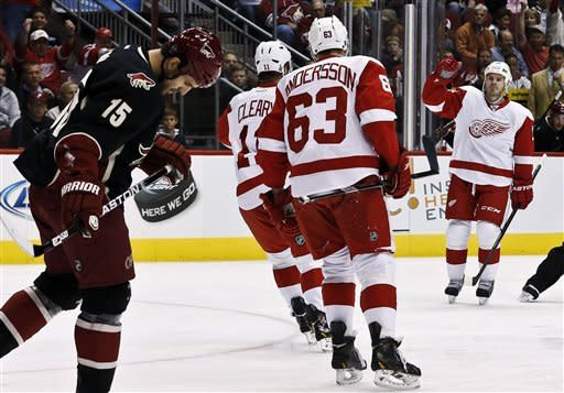 Detroit Red Wings' Ian White, right, celebrates his goal against the Phoenix Coyotes with teammates Joakim Andersson (63), of Sweden, and Daniel Cleary (11) as Coyotes' Boyd Gordon (15) skates past in the first period during an NHL hockey game, Monday, March 25, 2013, in Glendale, Ariz. (AP Photo/Ross D. Franklin)