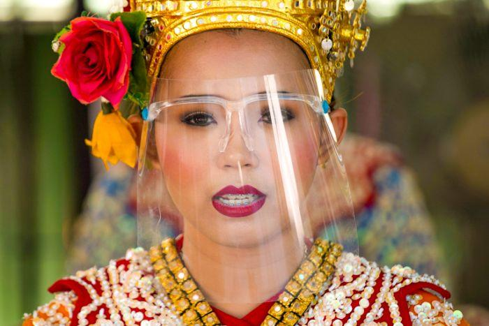 A woman in a Thai traditional outfit wearing a clear face shield