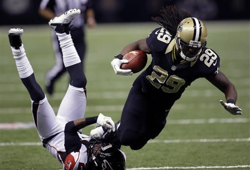 New Orleans Saints running back Chris Ivory (29) is tripped by Atlanta Falcons cornerback Dunta Robinson in the second half an NFL football game at Mercedes-Benz Superdome in New Orleans, Sunday, Nov. 11, 2012. (AP Photo/Bill Haber)