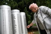 Zdravka Gvozdjar, mother of a murdered child, touches the monument for children killed during the siege of Sarajevo