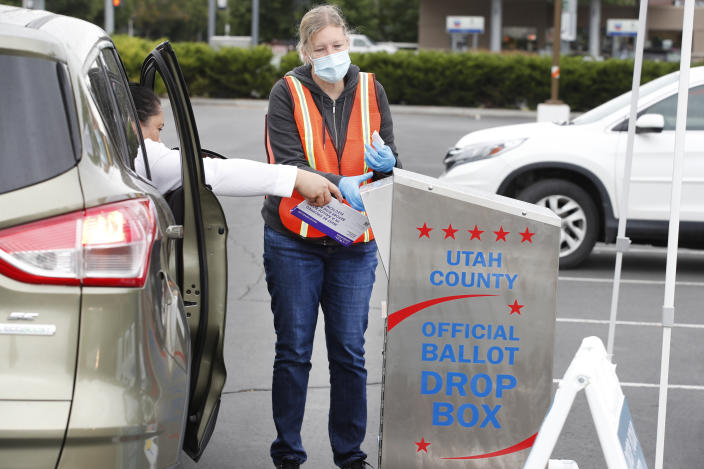 A women is helped by an election worker to put her ballot in a box while voting from her car in the parking lot of Lavell Edwards Stadium on the campus of Brigham Young University on June 30, 2020 in Provo, Utah.(George Frey/Getty Images)