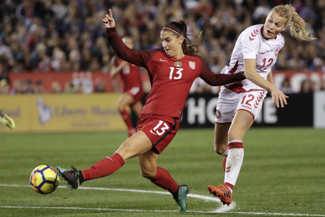 FILE - In this Jan. 21, 2018, file photo, United States forward Alex Morgan, left, shoots on goal as Denmark forward Stine Larsen, right, defends during the second half of an international friendly soccer match in San Diego. Shes already an internationally recognized soccer player with a World Cup title and an Olympic gold medal. Shes also the author of a series of kids books. Now you can add actor to Alex Morgans resume. The U.S. national team forward makes her theatrical debut in a new feature Alex & Me about a young player who is inspired by Morgan. (AP Photo/Gregory Bull, File)
