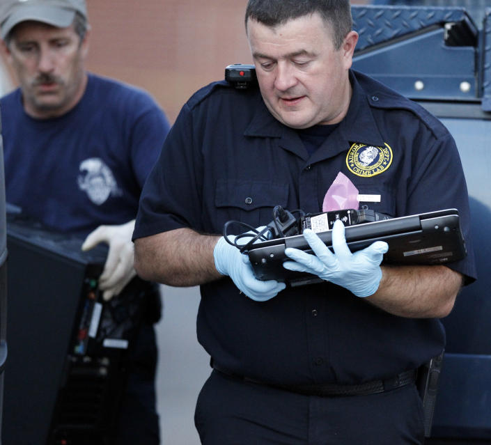 """Investigators remove computer equipment as evidence from the apartment of alleged gunman James Holmes, Saturday, July 21, 2012 in Aurora, Colo. Authorities reported that 12 died and more than three dozen people were shot during an assault at a movie theatre midnight premiere of """"The Dark Knight Rises."""" (AP Photo/Alex Brandon)"""