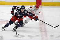 Columbus Blue Jackets' Alexandre Texier, left, carries the puck up ice as Detroit Red Wings' Adam Erne defends during the second period of an NHL hockey game Tuesday, March 2, 2021, in Columbus, Ohio. (AP Photo/Jay LaPrete)