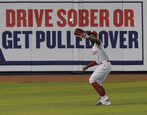 Philadelphia Phillies left fielder Andrew McCutchen catches a ball hit by Miami Marlins' Garrett Cooper to end the first inning of a baseball game, Thursday, Sept. 10, 2020, in Miami. (AP Photo/Wilfredo Lee)