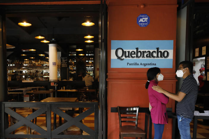"A young couple waits for their takeout order outside Argentine grill Quebracho, in the Cuauhtemoc neighborhood of Mexico City, Sunday, Jan. 10, 2021. Worried about its survival, Quebracho is one of many restaurants in the capital and adjacent Mexico State which are banning together in a campaign dubbed ""Abrir o Morir,"" Spanish for ""Open or Die,"" and plan to open their doors to diners again on Monday in defiance of ordinances limiting restaurants to takeout service while the Mexico Valley remains under a COVID-19 pandemic red alert. (AP Photo/Rebecca Blackwell)"