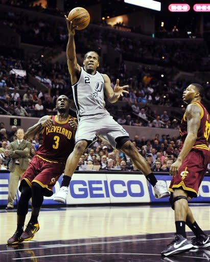 San Antonio Spurs forward Kawhi Leonard (2) shoots between Cleveland Cavaliers' Dion Waiters (3) and Alonzo Gee (33) during the first half of an NBA basketball game, Saturday, March 16, 2013, in San Antonio. (AP Photo/Bahram Mark Sobhani)