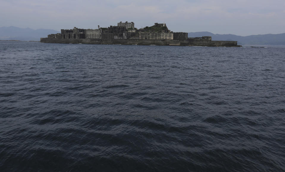 "FILE - In this June 29, 2015, file photo, Hashima Island, commonly known as Gunkanjima, which mean ""Battleship Island,"" is seen off Nagasaki, Nagasaki Prefecture, southern Japan. Gunkanjima was among the settings for a dark chapter in Japan's history, when hundreds of thousands of people were brought from the Korean Peninsula and other Asian nations to work in logging, in mines, on farms and in factories as forced labor. (AP Photo/Eugene Hoshiko, File)"