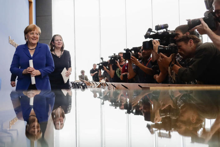 <p>Photographers and television cameras cover German Chancellor Angela Merkel as she leaves a news conference in Berlin, Germany, July 28, 2016. Second left is Angela Wefers, the journalist who led the news conference. (Photo: Markus Schreiber/AP)</p>