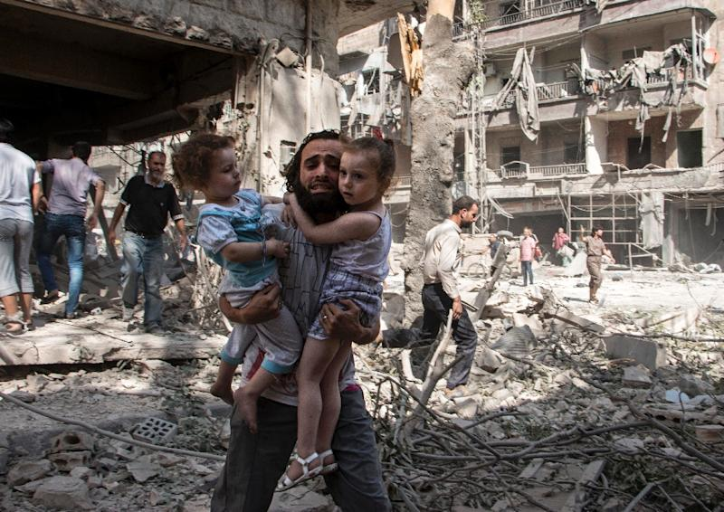 A Syrian man carries his two girls across the rubble following a barrel bomb attack on the rebel-held al-Kalasa neighbourhood of Aleppo in September 2015